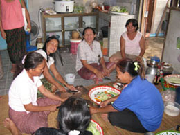 crowds of women gather in groups to make food for the monks