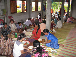 some villagers stay to eat breakfast after the monk